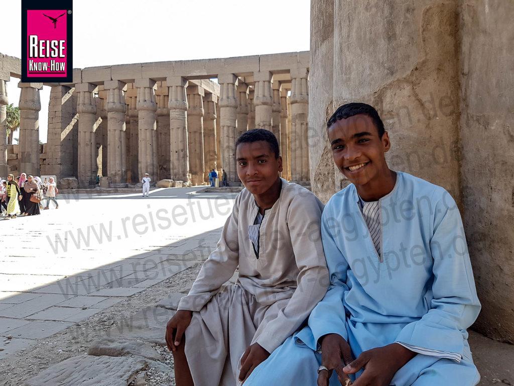 Zwei ägyptische Jungen in Galabiya sitzen an einer Säule im Luxor-Tempel