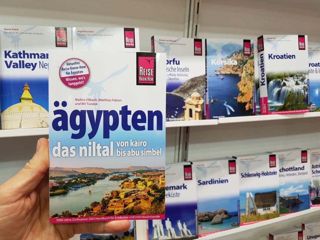 Niltalführer vor Regal mit Reise Know-How-Reiseführern auf der Leipziger Buchmesse